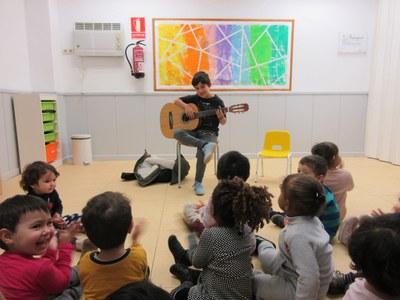 El Guillem toca la guitarra per totes les nenes i nens de l'escola